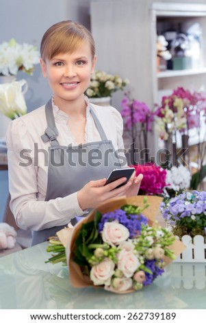 New call to make another beautiful bouquet. Close-up of a young smiling florist holding a mobile phone in hands standing by the counter of the flower shop - stock photo