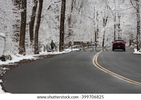 New Canaan, CT, USA - April 21, 2016: A car and a jogger on a road on April 21, 2016 in New Canaan, Connecticut