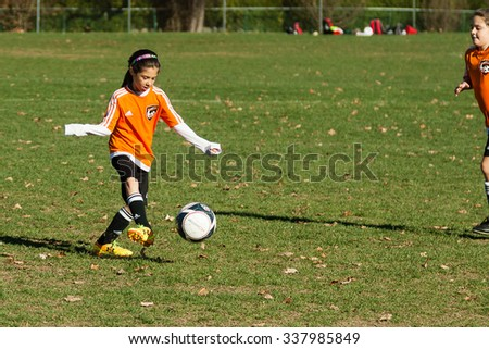 New Canaan, CT, USA - November 8, 2015: Daytime scene of young girls in an all girls team in New Canaan, Connecticut on November 8, 2015 while playing an organized youth soccer game