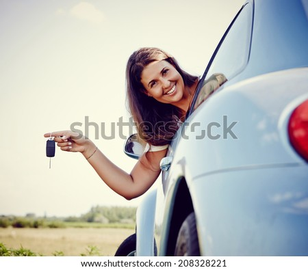 New car - driver woman Holding Her new Car keys out of the window, smiling looking into Camera. More of Her: - stock photo