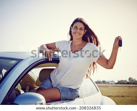 New car - Happy smiling woman is showing keys to her new car, rental car. - stock photo