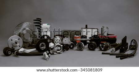 New car parts on a gray background closeup. Large range of new car parts service station - stock photo