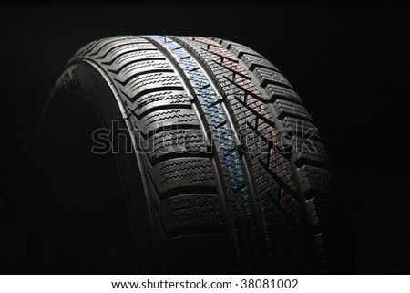 New car tire close up on black background - stock photo