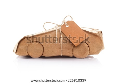 New car wrapped in recycled brown wrapping paper - stock photo