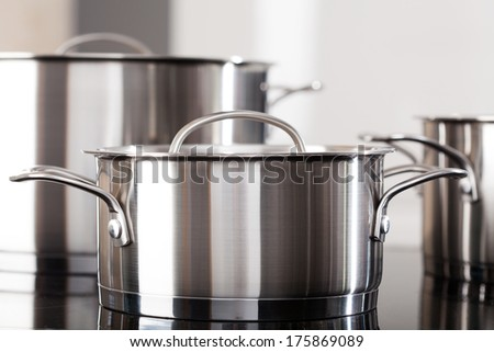 New clean aluminum pots on the kitchen top - stock photo