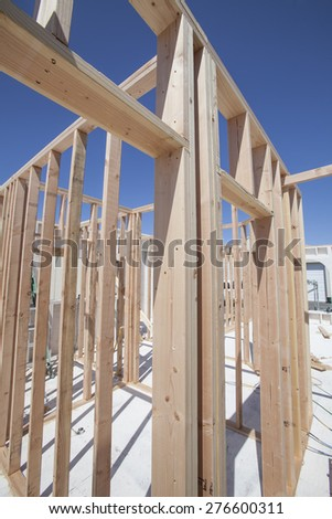 New construction home framing against a blue sky and sun - stock photo