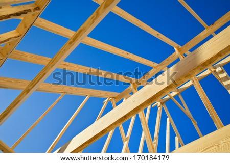 New construction home framing against blue sky, closeup of ceiling frame. - stock photo