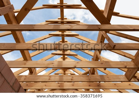 New construction home framing against blue sky, closeup of ceiling frame. - stock photo