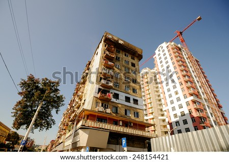 new construction on the background of the old house - stock photo