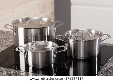 New cookware set on black induction hob in modern kitchen - stock photo