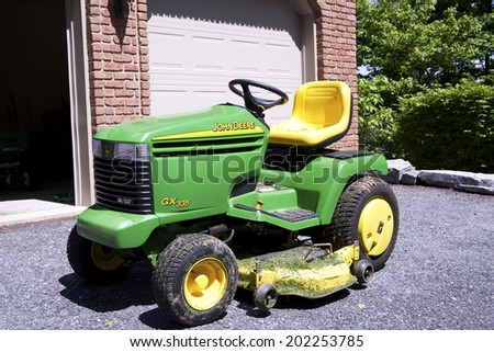 New Cumberland, PA, USA - May 21, 2011 :John Deere lawn mower in front of modest home