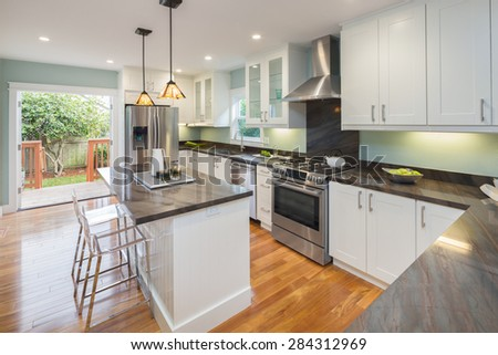 New decorated white Kitchen in luxury home with black granite counter top, kitchen island, bar stools and wooden floor. - stock photo