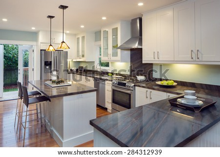 New decorated white Kitchen in luxury home with black granite counter top, kitchen island, modern black chrome bar stools and wooden floor. - stock photo
