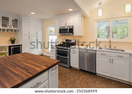 New decorated white Kitchen in luxury home with kitchen island and wooden surface. In addition an amazing new Cork Floor. - stock photo