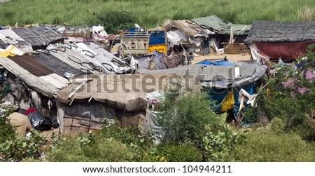 NEW DELHI, INDIA - AUGUST 3: Small slum near capital New Delhi on August 3, 2011 in India. Over 40 million Indian people live in slums. - stock photo