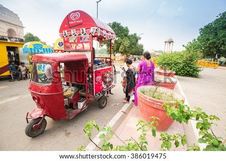 NEW DELHI, INDIA - AUGUST 4,2015 : The colorful soft drink and ice cream motorcycle shops are at the road side in public park around Indian gate in summer. - stock photo