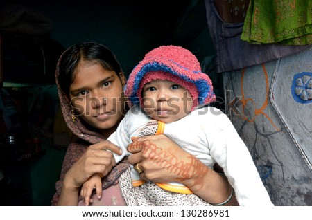 NEW DELHI,INDIA-FEBRUARY,4: a young Indian mother with her child who lives in the poorest district of New Delhi in February 4,2013.50% of the population of New Delhi is thought to live in slums - stock photo