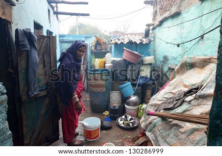 NEW DELHI,INDIA-FEBRUARY 4 :An unidentified woman in the courtyard of his house in New Delhi in February 4,2013. 50% of the population of New Delhi is thought to live in slums - stock photo