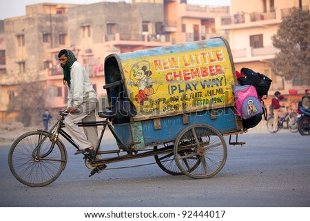 NEW DELHI, INDIA - JANUARY 23: Indian man drives kids to school on Republic Day on January 23, 2011 in New Delhi, India. Republic Day commemorates the date on which the constitution of India began. - stock photo