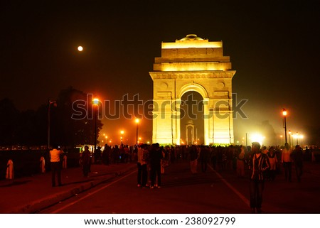 NEW DELHI, INDIA, NOVEMBER 07, 2014: India gate against the moonlit sky. Visitors throng at the famous War memorial, a tourist attraction. Misty cityscape lit by streetlights and the full moon. - stock photo