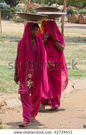 NEW DELHI - JUN 27: Young unidentified Indian women in colorful traditional dresses carry things on their heads in New Delhi, India on a Sunday morning. 27th June, 2010. - stock photo