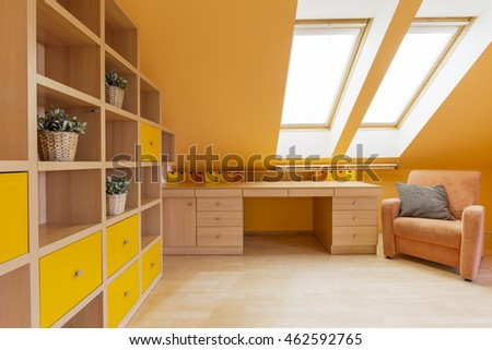 New design attic room in orange with wall shelving unit, desk and armchair