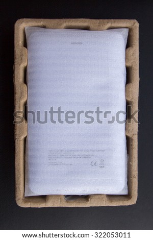 New digital tablet, packaged in carton and wrapped in protective pouch before being released. View from the back side. Isolated on black background  - stock photo
