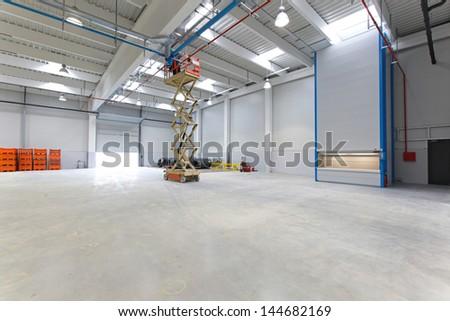 New distribution warehouse hall with hydraulic scissors lift platform - stock photo