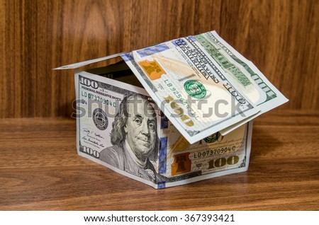new dollar house, money building, isolated on wooden background - stock photo