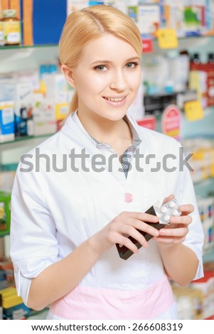 New effective medication. Vertical shot of a smiling female pharmacist holding a blister of pills in her hands - stock photo