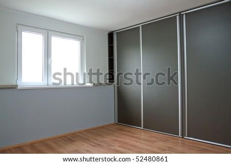 New empty bedroom with window and wardrobe - stock photo