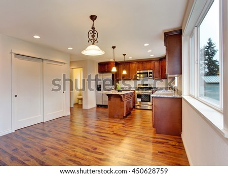 New empty dining room and kitchen interior with hardwood floor. Small bathroom