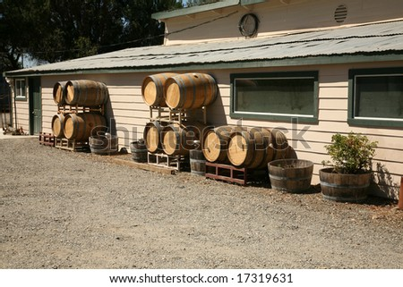 """New Empty Wine Barrels lay against a building in Sonoma County California  aka """"The Other Wine Country"""" - stock photo"""