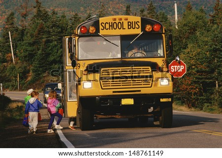 NEW ENGLAND - CIRCA 1980's: Children boarding a yellow school bus, New England - stock photo