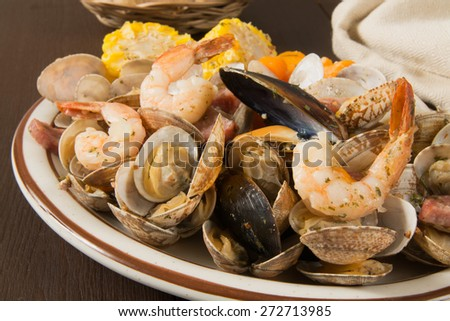 New England style clam bake with shrimp, mussels and corn on the cob - stock photo