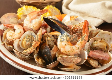 New England style clam bake with shrimp, mussels, corn and potatoes - stock photo