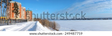 New estate on the Kama river coast. Winter panorama. Residential complex on the banks. Scenic cold day landscape. - stock photo
