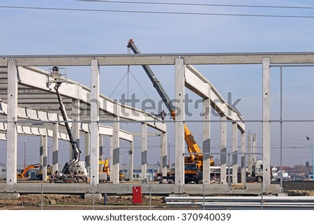 new factory construction site with workers and machinery - stock photo