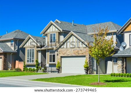 New family house on sunny day with landscaped lawn in front and blue sky background. New house with concrete driveway and asphalt road in front. - stock photo
