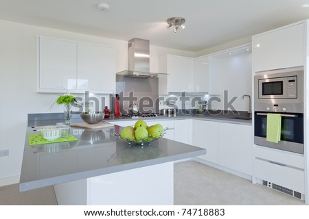 New fitted modern kitchen with built in stainless steel appliances and breakfast bar. - stock photo