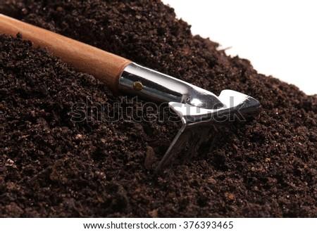 New garden rake on the organic soil over white background - stock photo