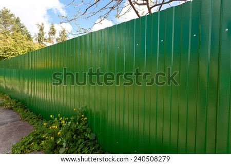 New green metallic fence in village - stock photo