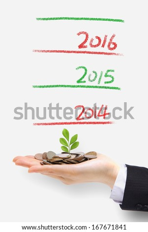new green plant sprouting from a hand with money with 2014 new year ,concept for business, growth and money - stock photo