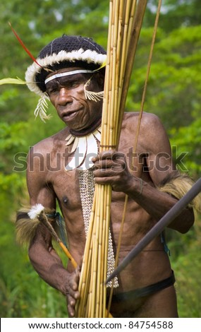 NEW GUINEA, INDONESIA -DECEMBER 28: The warrior of a Papuan tribe in traditional clothes and coloring in New Guinea Island, Indonesia on December 28, 2010