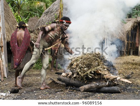 NEW GUINEA, INDONESIA -DECEMBER 28: Unidentified warrior of a Papuan tribe uses an earth oven method of cooking pig, in New Guinea Island, Indonesia on December 28, 2010 - stock photo