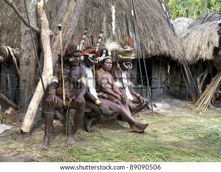 NEW GUINEA, INDONESIA -DECEMBER 28: Unidentified warriors of a Papuan tribe in traditional clothes and coloring sit in front of their home in New Guinea Island, Indonesia on December 28, 2010. - stock photo