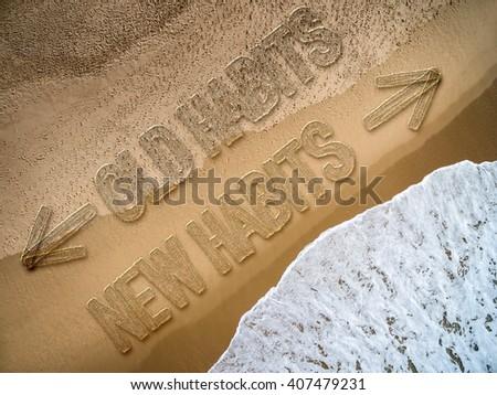 New Habits - Old Habits written on the beach - stock photo