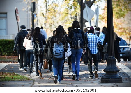 NEW HAVEN, USA - NOV 14, 2015: People walk along a beautiful tree lined path on the campus of Yale University. Founded in 1701 the ivy league college has a current enrollment of over 12,000 students. - stock photo