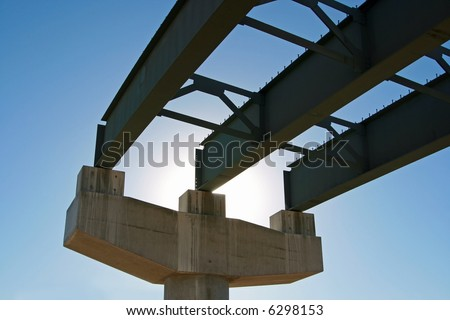 New highway bridge being built - viewed from underneath and looking toward the sun. This portion of the bridge is incomplete and there's no road decking. - stock photo