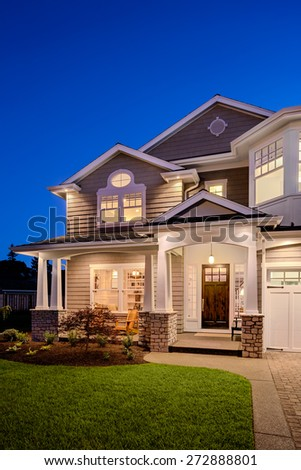 New Home at Night: Luxury Home Exterior with Deep Blue Sky. Vertical orientation - stock photo